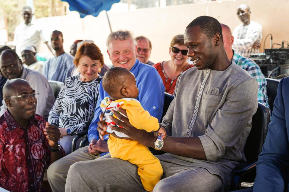 Gorgui Dieng and Timberwolves season ticket holders Roger and Nancy McCabe at a hospital dedication ceremony in Dakar, Senegal in July, 2019.