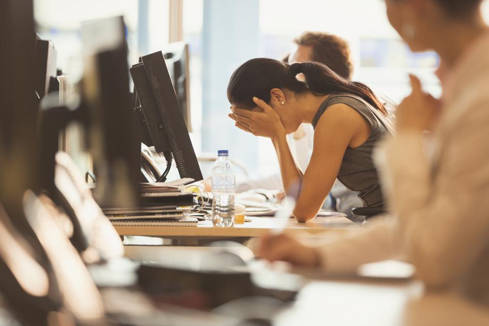 Stressed businesswoman with head in hands at office desk