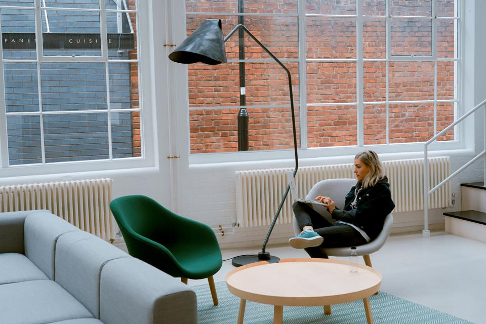A woman sitting on a chair working in an empty room.