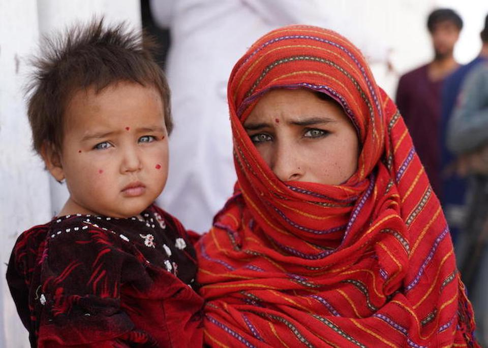 In December 2019, 12-year-old Yasamin holds her baby sister, Aisha Gul, outside a nutrition center in a camp for internally displaced people near the city of Herat in western Afghanistan.
