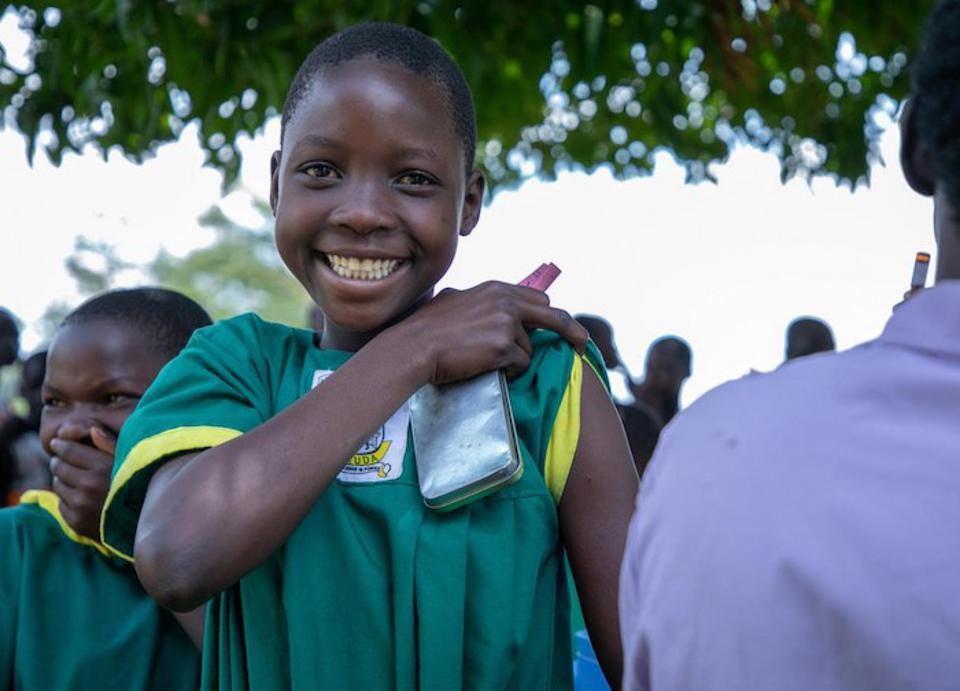A student at Aguket Primary School in Uganda's Busia District prepares to be vaccinated against measles, mumps, rubella and polio during a 2019 nationwide immunization campaign run by the Ugandan Government with support from UNICEF and WHO.