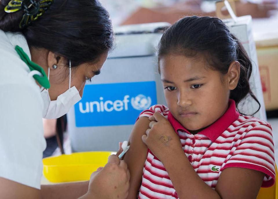 Senerita, 9, receives her measles shot in Leauvaa Village, Samoa. The item behind her (bearing the UNICEF logo) is a cold box, a vital piece of equipment for safely transporting vaccines.