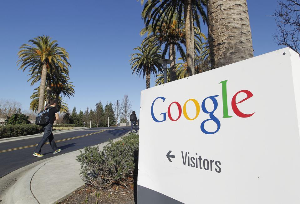 A man walks past company signage at Google Inc. headquarters in Mountain View, California. Tony Avelar