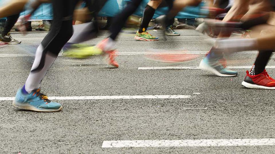 A close-up of runners' feet as they run down a paved street.