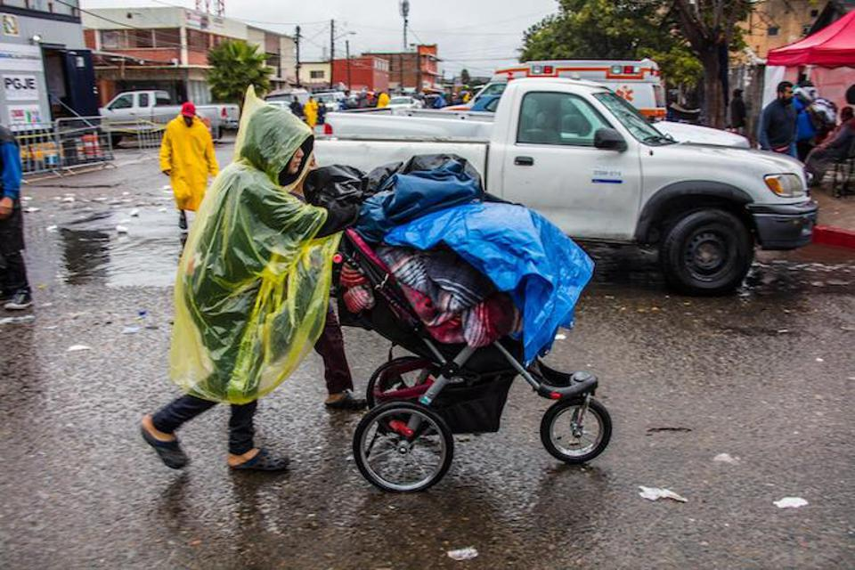 A family migrating from Central America to the U.S. leaves a makeshift shelter during a rain storm in Tijuana, Mexico. Homicide rates in Tijuana rose to 138 killings per 100,000 residents in 2018, or about seven murders on average per day.
