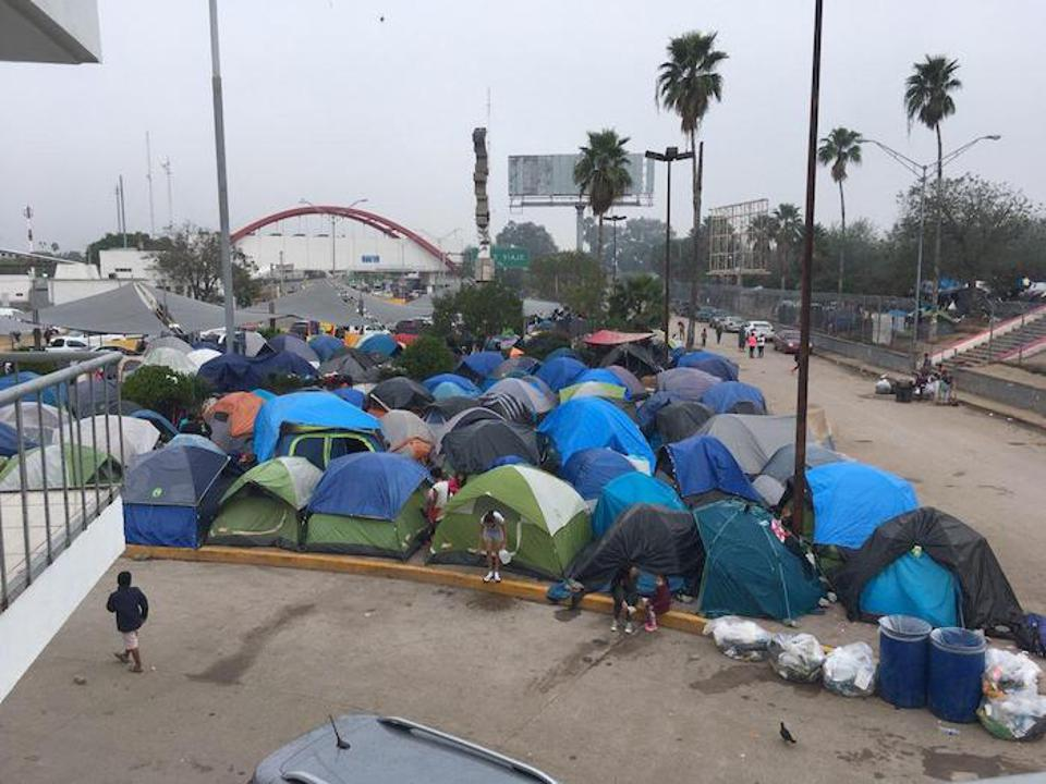 Families seeking asylum in the U.S. have formed a tent encampment in Matamoros, Mexico near the red-arched port of entry building, visible in the distance.