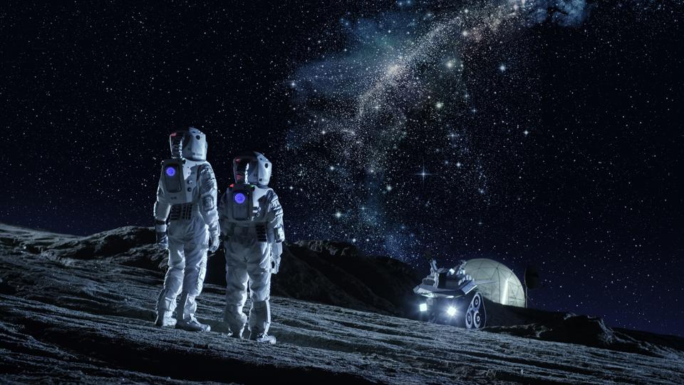 Two Astronauts in Space Suits Stand on the Planet and Looking at the The Milky Way Galaxy. In the Background Lunar Base with Geodesic Dome. Moon Colonization and Space Travel Concept.