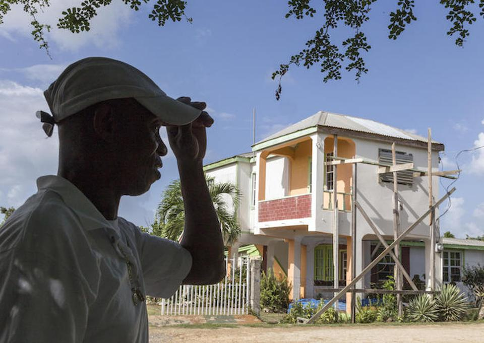 On the island of Barbuda, James Gerald, Sr. stands in front of his family's home, damaged by Hurricane Irma. He looks forward to being reunited with his wife and children one day.  ″I'd like to be there for them as a father, every day,″ he says.