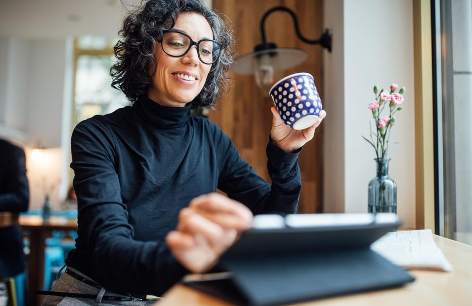 Woman at cafe using digital tablet at coffee shop