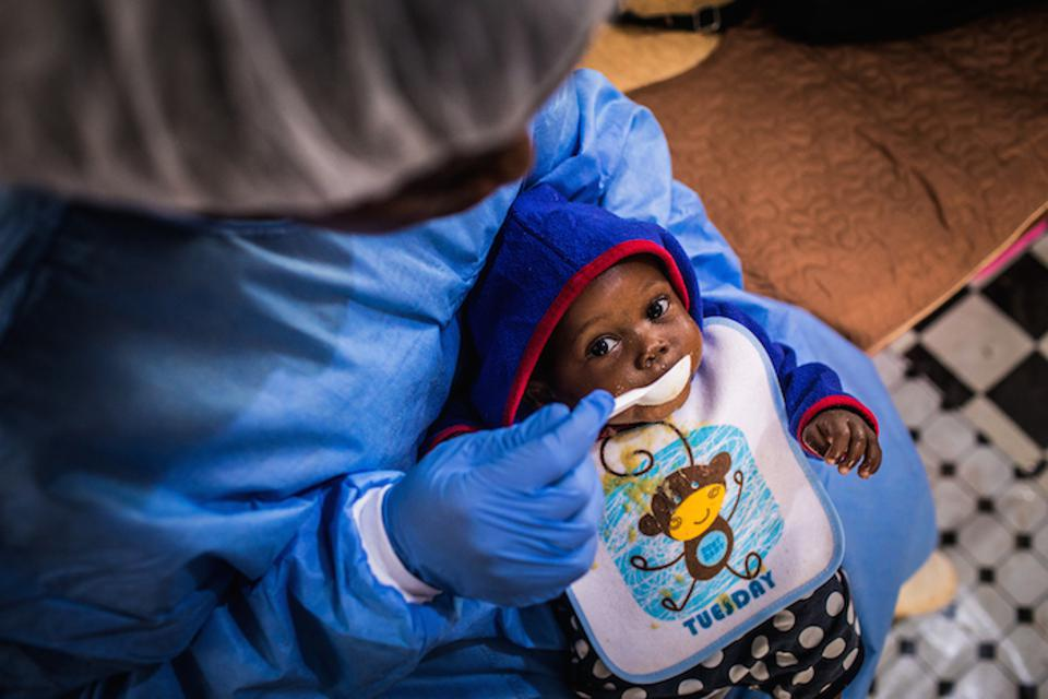 A UNICEF supported caregiver in the Democratic Republic of Congo feeds a baby whose mother has died after being infected with the Ebola virus.