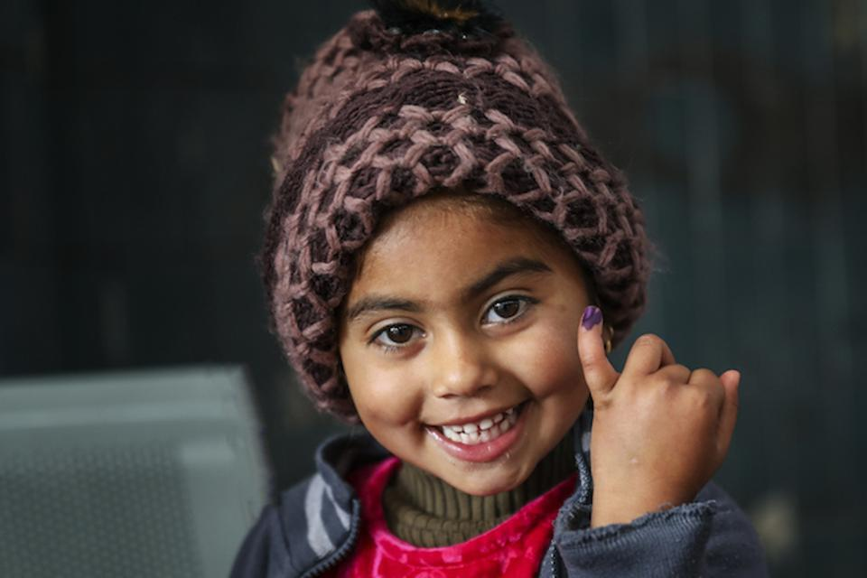A girl in Pakistan shows the ink mark on her finger that she received after being vaccinated against polio during a UNICEF supported immunization campaign.