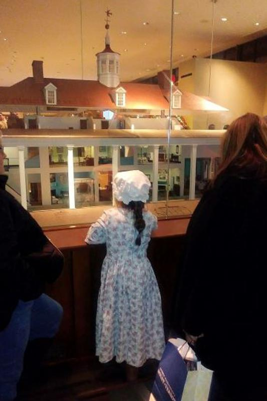 young girl looks at copy of Mount Vernon