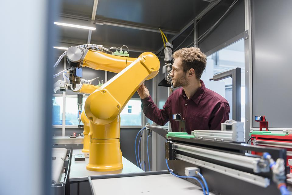 Businessman checking industrial robot in high tech company