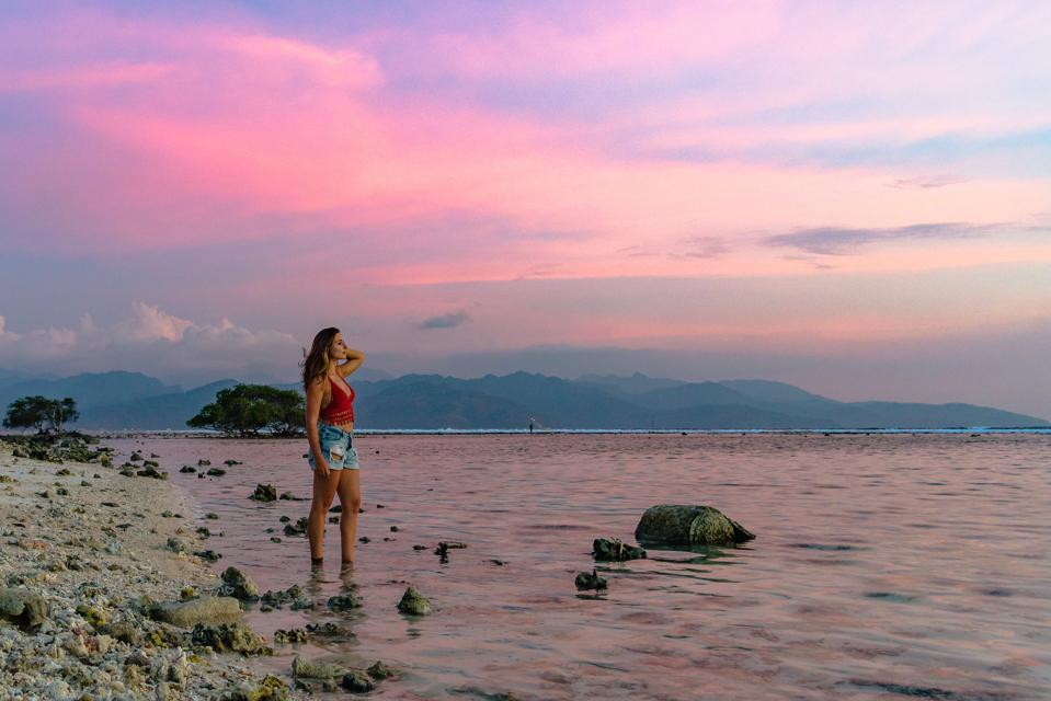 attractive woman looking out into pink sunset by the beach in indonesia