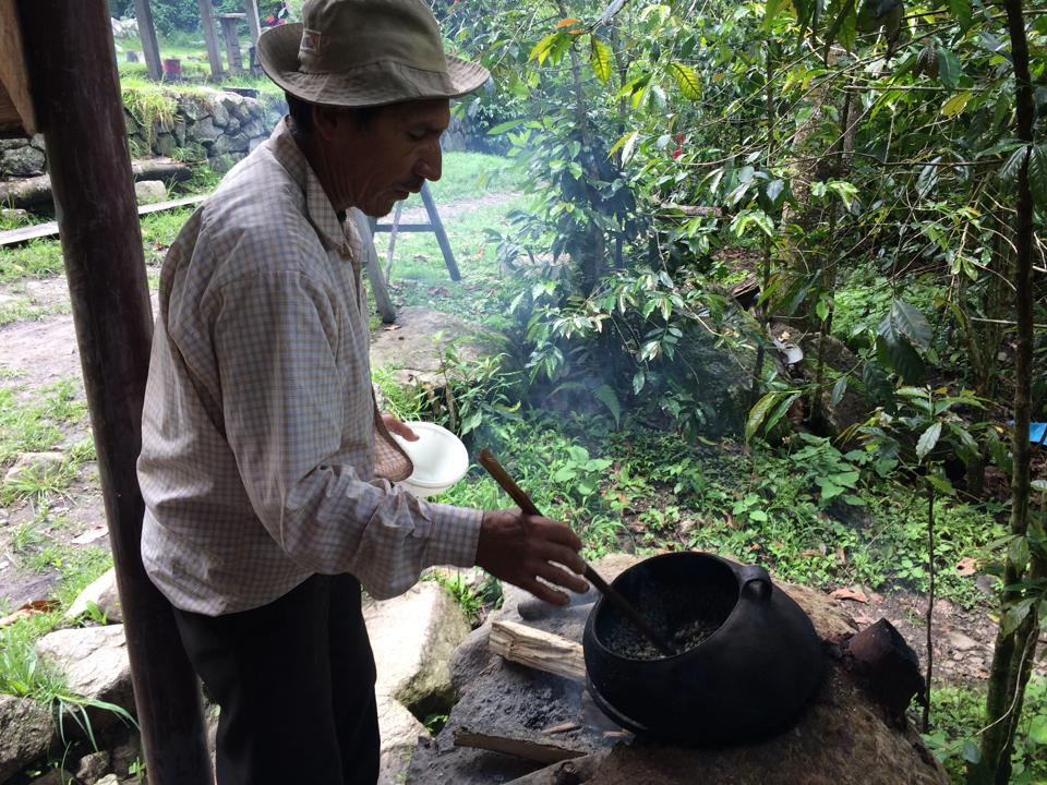 Alpaca's treks include stops at local villages. Here, a man roasts coffee over an open fire.