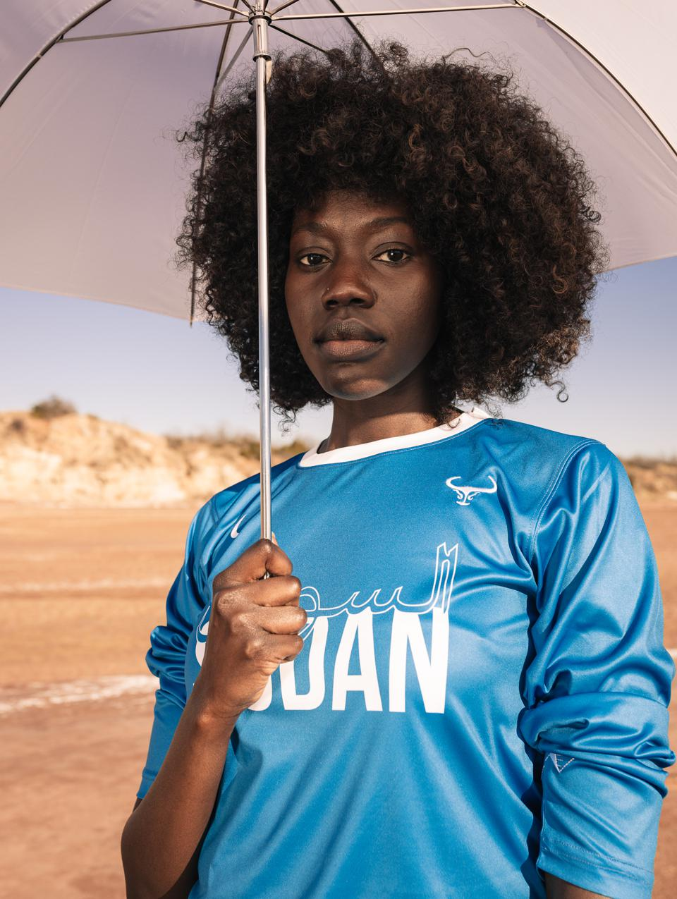"""""""What the world witnessed in 2019 demonstrates there is so much hope for the change we envision for our countries. The power is in the people and there can be solidarity amongst the people of Sudan and South Sudan. I believe the release of this jersey honors that."""" - Grace Lul, Sudanese model depicted."""