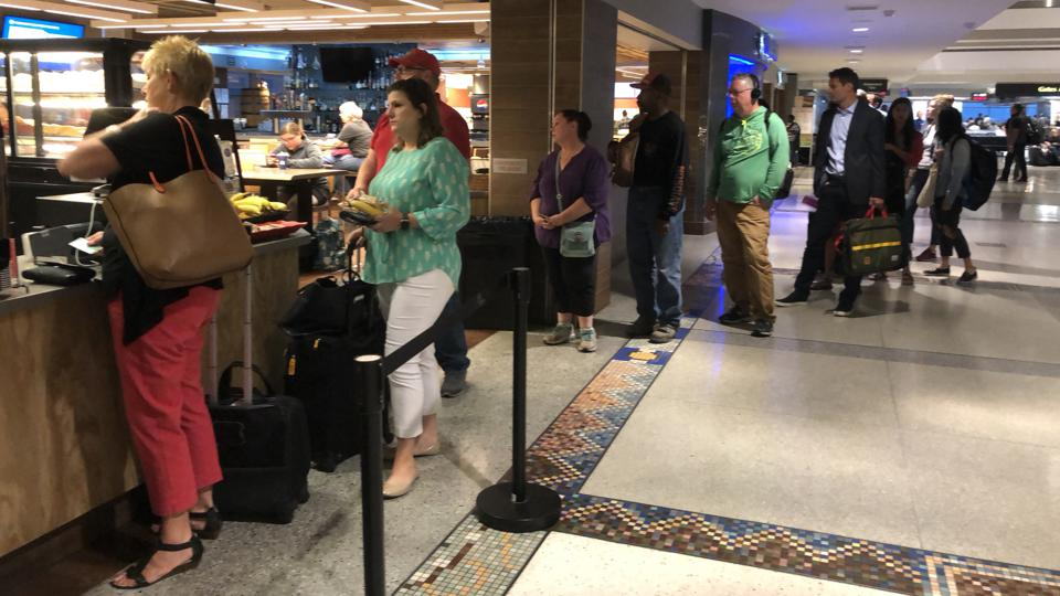 A long line of people wait in line for coffee at an airport shop in the morning.