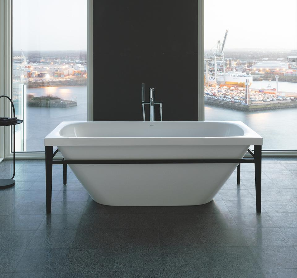 This industrial looking freestanding  tub is set in a supporting metal frame. The rectangular shape of the frame shows off the gentle curves of the tub.