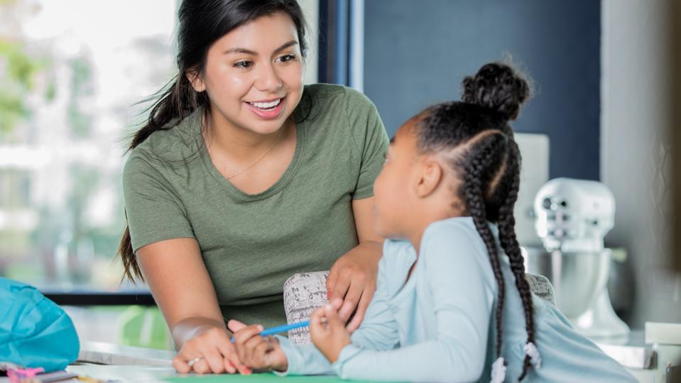 Happy young Hispanic woman is tutoring elementary age girl.