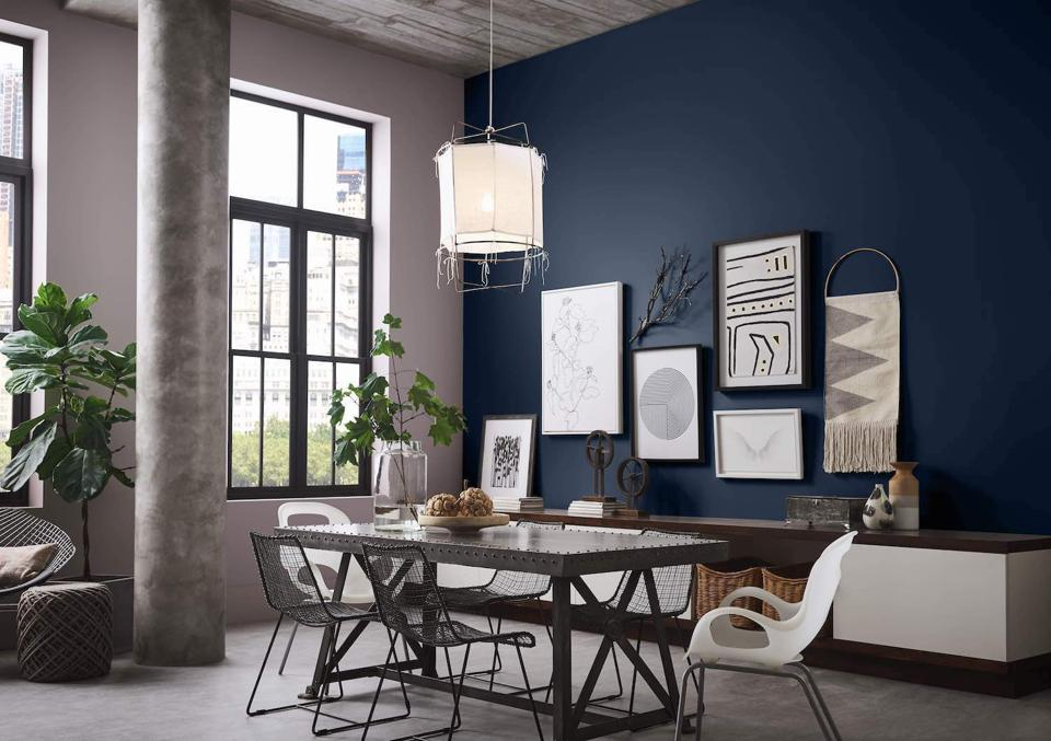 An example of a feature wall in the navy color predicted as a key color for the new year by Sherwin-Williams for this dining room.