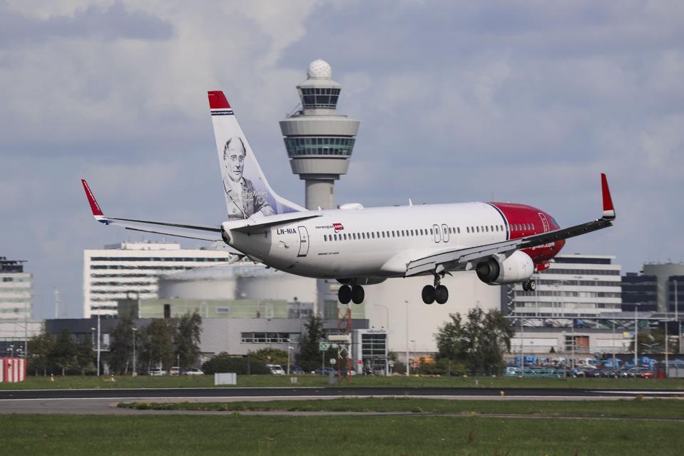 A Norwegian Air Shuttle Boeing 737-800 landing at Amsterdam Schiphol International Airport, the Netherlands.