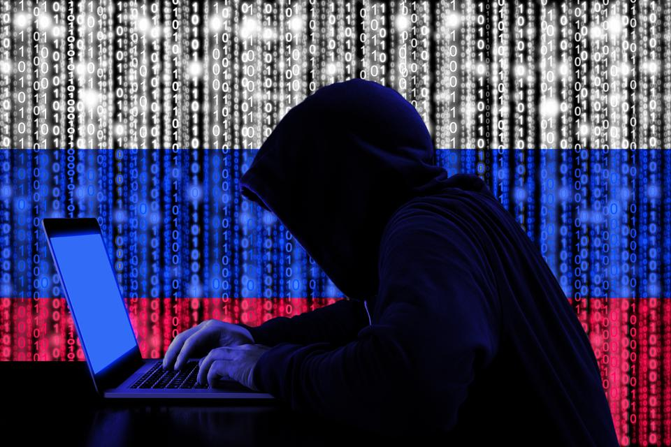 Hacker from Russia at work against a Russian flag composed of binary code