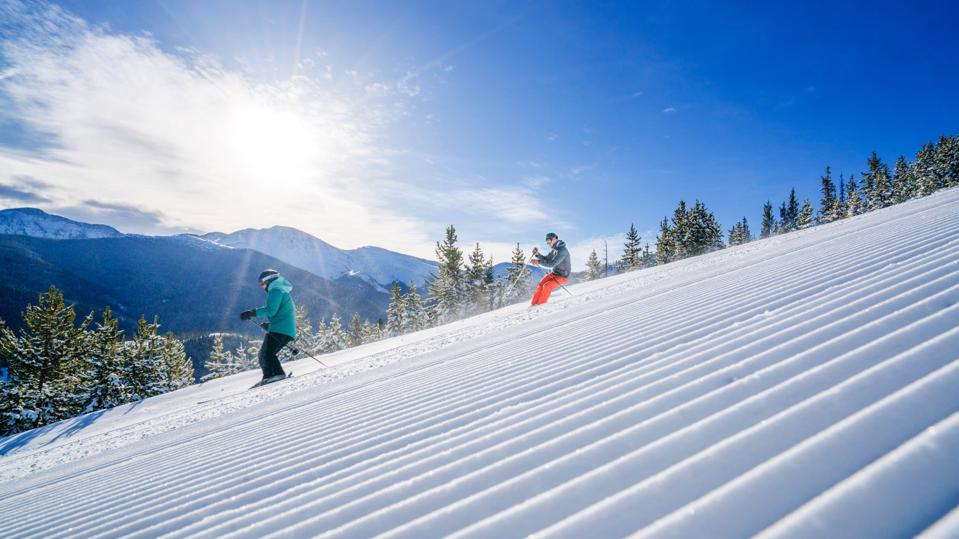 Two skiers cruise down groomed trails at Winter Park Resort.