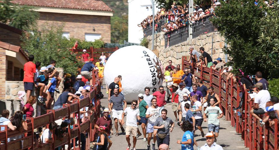 people running in front of giant balls in the streets of Spain