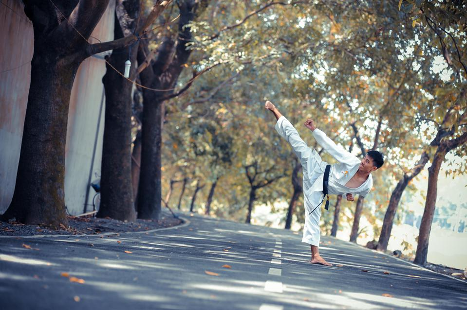 man wearing karate gi standing on road