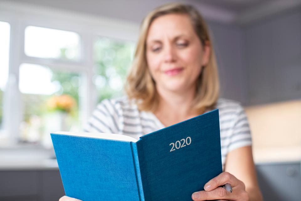 Woman Opening New Year 2020 Diary On Table At Home