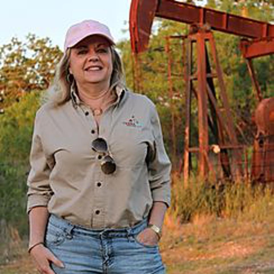 Marsha Hendler in the field with a pump jack in the background.