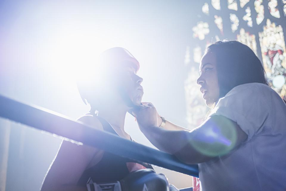 a woman adjusts a female boxer's chinstrap