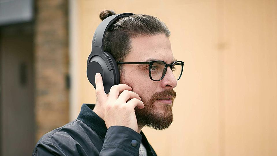 Person wearing a pair of black Sony WH-H900N headphones.