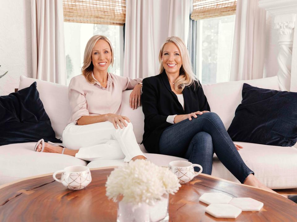 Melanie Petschke and Kelly Weston sit on a sofa in front of a coffee table.