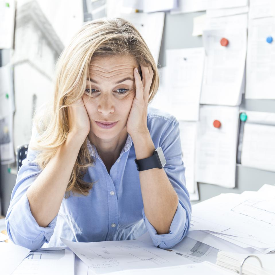Stressed woman sitting at desk in office surrounded by paperwork