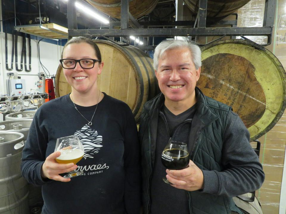 Courtney Servaes, the owner of the Servaes Brewing Company in Shawnee, Kansas, enjoys a New England-style IPA, Given To Fly, as beer expert Pete Dulin hoists Rise Up, a Mexican chocolate stout.