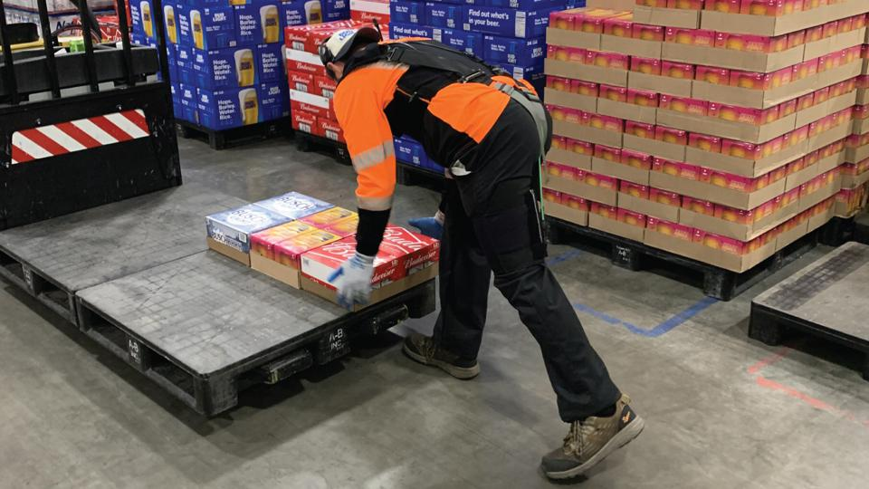 Caption: Warehouse worker using a HeroWear lift-assist exosuit on the job to reduce strain on his back muscles while loading pallets. It is not uncommon for workers to perform 100-300 lifts per hour.