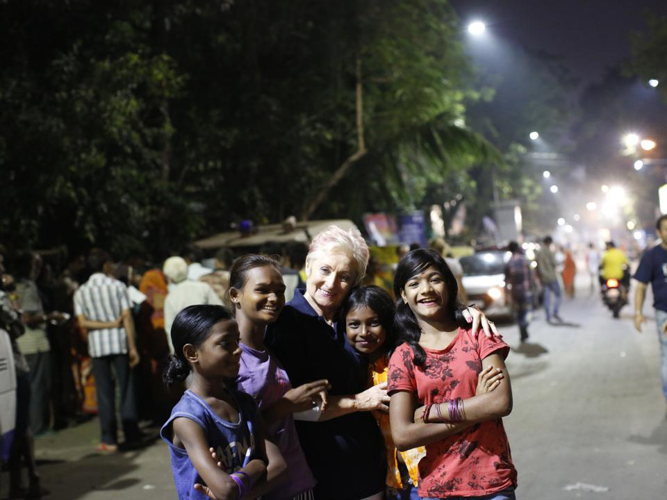 Maureen Forrest poses with 4 Indian children on the streets of Kolkata.