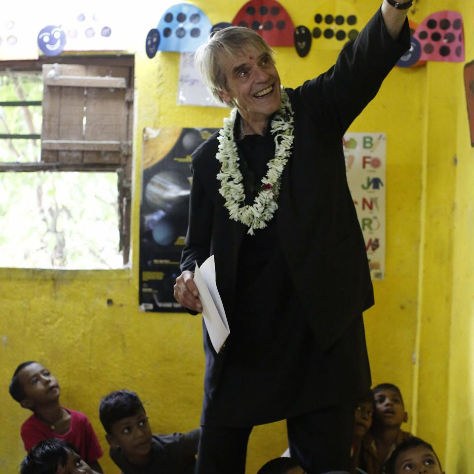 Jeremy Irons points at the ceiling in a classroom filled with children.