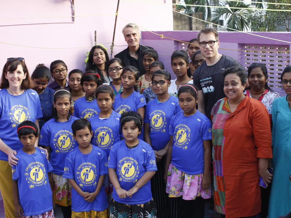 Several adult volunteers and teachers stand with a group of Indian children.