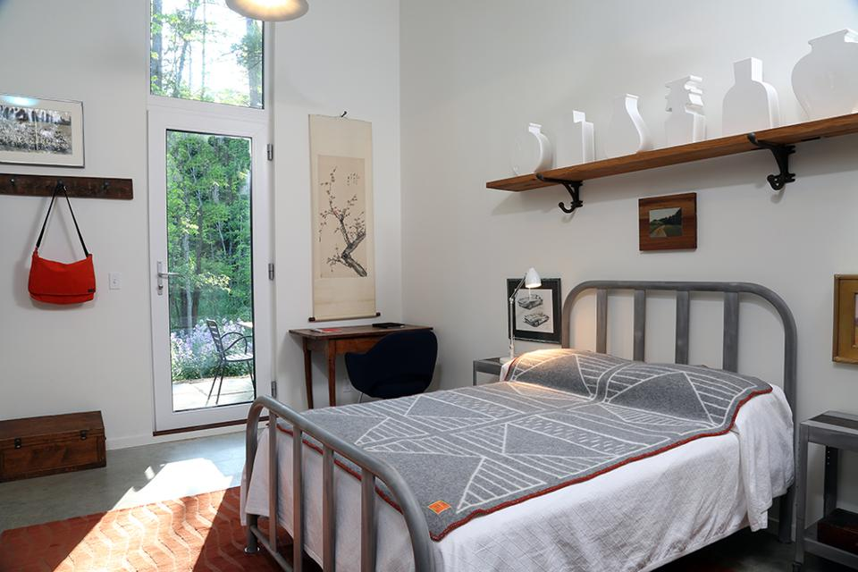 The bedroom is light and open with high ceilings The shelf over the bed is from 300-year-old wood, held up by large metal barn saddle hooks.