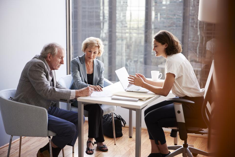 Senior Couple Signing Document In Meeting With Female Financial Advisor In Office