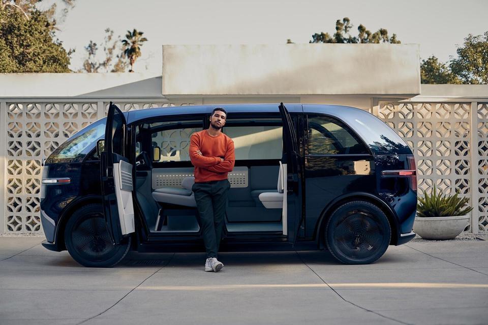 Canoo subscription EV with man standing in open doors.