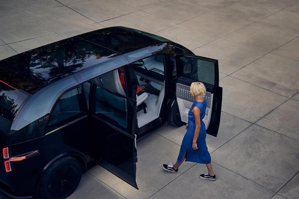 Canoo EV with woman approaching.