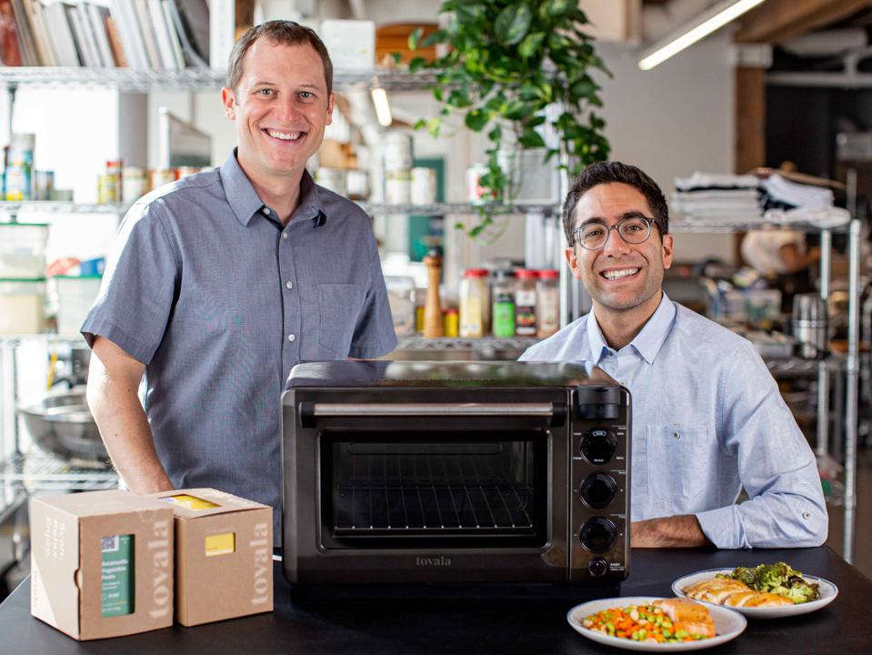 Wilcox and Rabie pose behind a small oven and two plates of cooked food.
