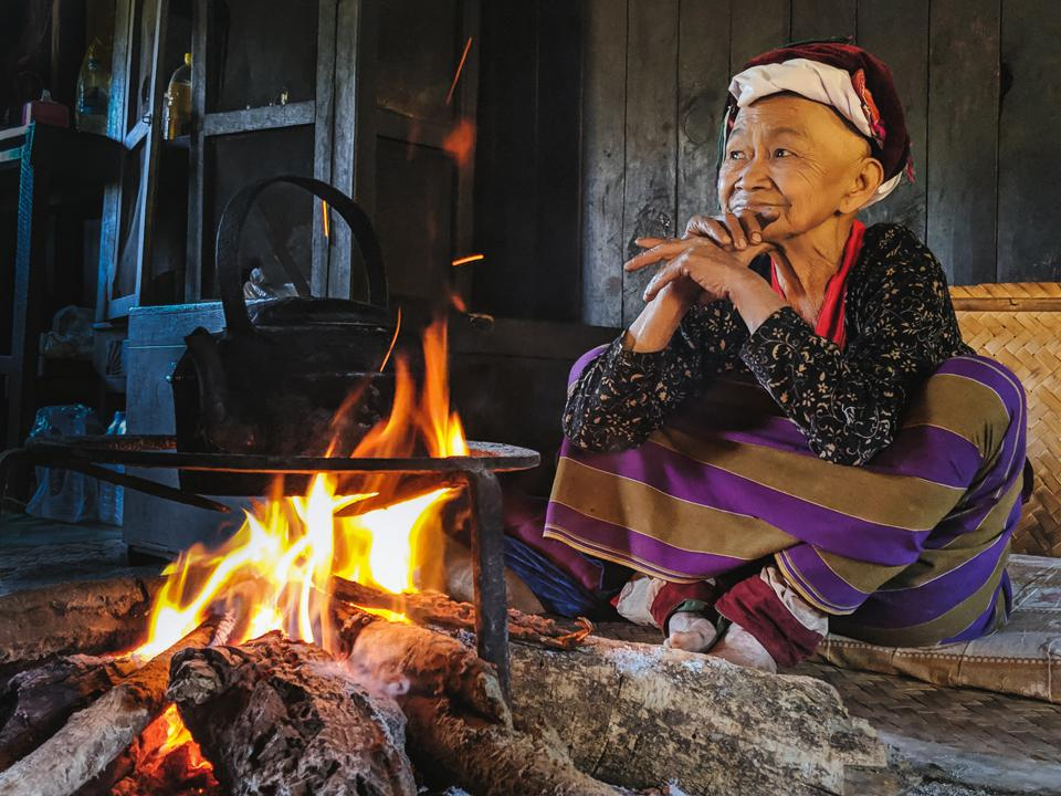 Old lady by the fire in Pankham Village, Myanmar