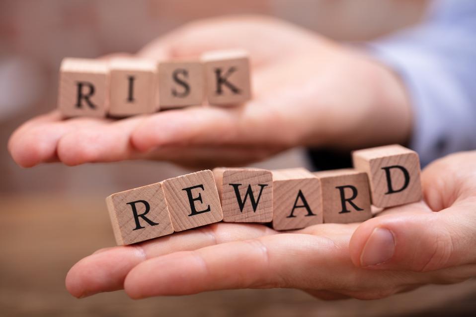 Businessman Holding Risk And Rewards Blocks