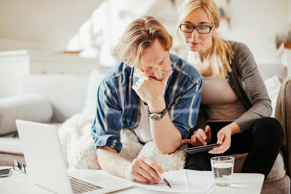 Distressed couple looks over their bank statements