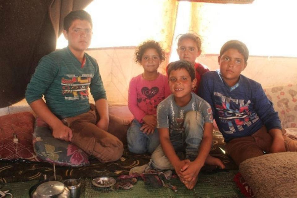 Hasan, 8, front and center, and his four siblings live in a camp for displaced persons in northern Idlib, Syria, one of many camps where a self-learning program, created by UNICEF in partnership with Educate A Child, is helping out-of-school kids.