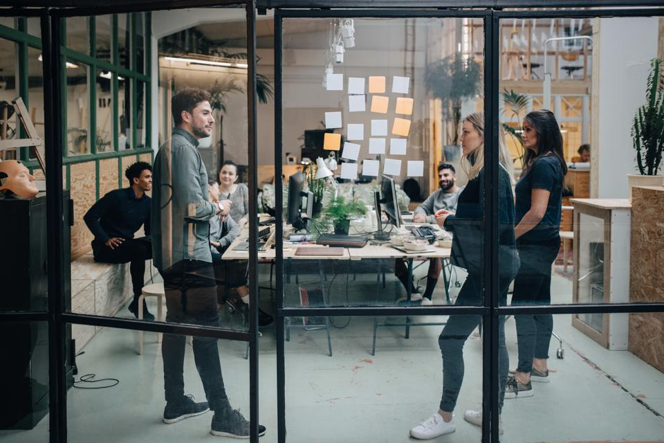 Business colleagues brainstorming in meeting at office seen through glass wall